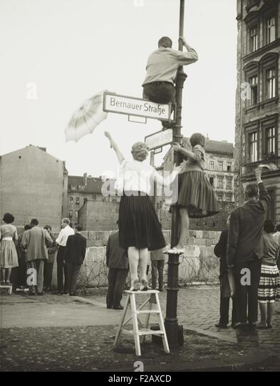 West Berliners in the French sector waved to friends and relatives in East Berlin. At Bernauer Strasse they used - Stock Image