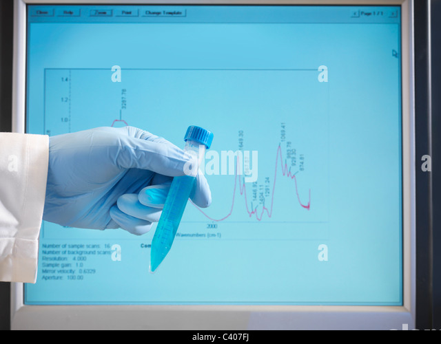 Hand holding sample in front of monitor - Stock Image