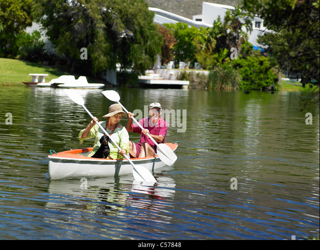 Older couple rowing canoe on lake - Stock Image