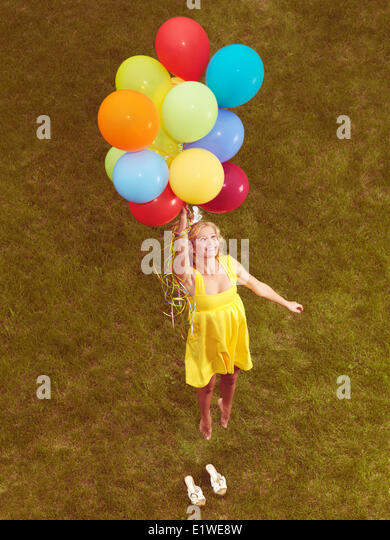 Happy young woman in yellow summer dress flying up from the ground with colorful helium balloons, retro stylized - Stock Image