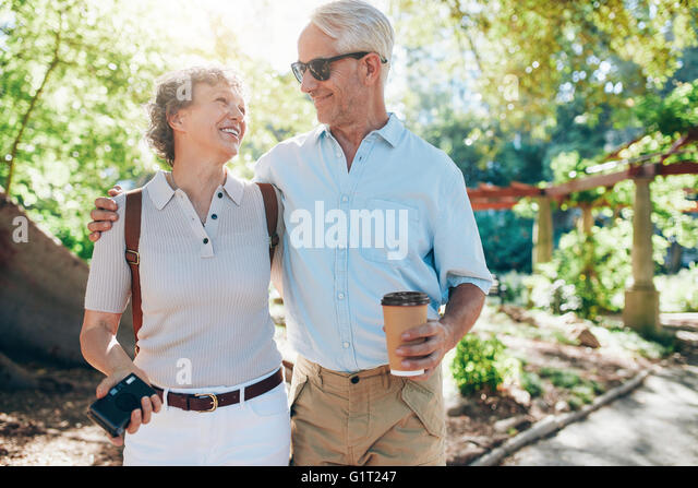 Portrait of happy mature couple walking together in a park. Husband and wife on a vacation. - Stock-Bilder