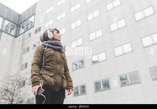 Low angle view of mid adult woman listening to headphones looking at city office block - Stock-Bilder
