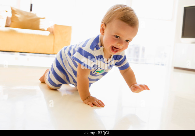 Baby crawling in living room - Stock Image