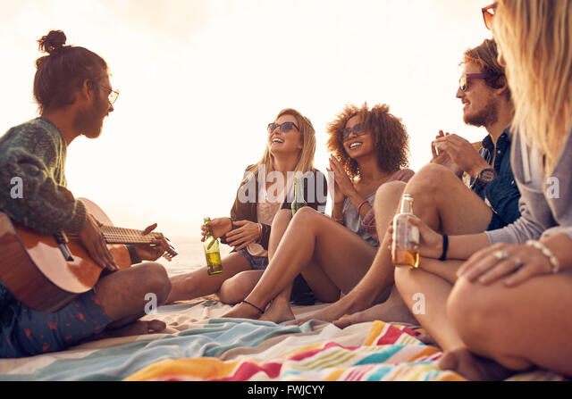 Happy hipsters relaxing and playing guitar at the beach. Friends drinking beers and listening to music. Having fun - Stock Image