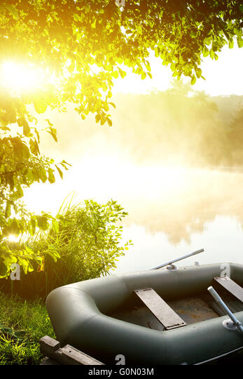Inflatable fishing boat on the bank of a river - Stock Image