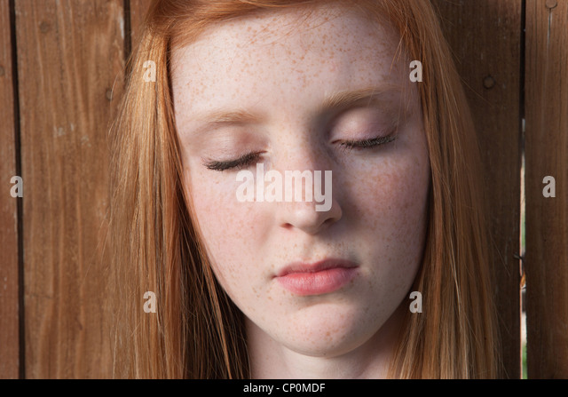 Fifteen year old girl looking serene with eyes closed outdoors. - Stock Image