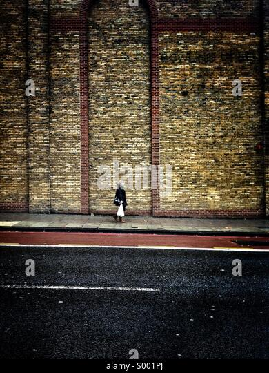 Woman walking past a wall. - Stock-Bilder