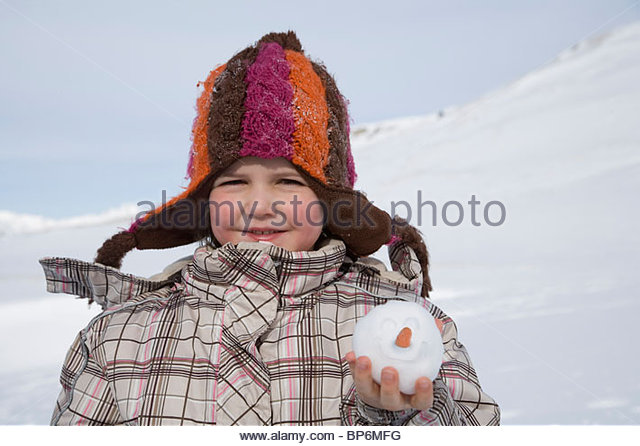 Portrait of young girl holding snowball with smiley face and carrot nose - Stock Image