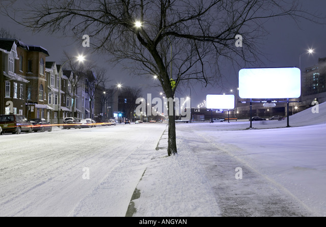 bare white billboards at night with the ground covered with snow, Montreal, Quebec, Canada. - Stock Image