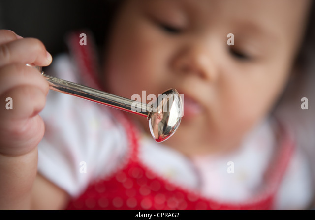 Japanese baby girl holding a sterling silver rattle. - Stock Image