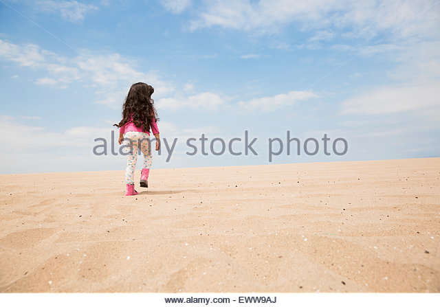 Girl with long hair walking up beach slope - Stock Image