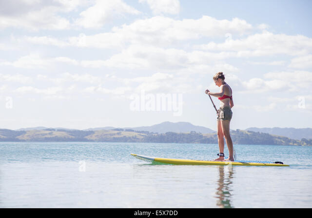 Mid adult woman stand up paddleboarding at sea - Stock Image