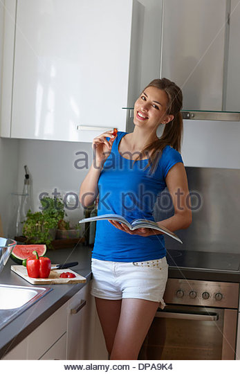 Woman holding up book and slice of red pepper - Stock Image