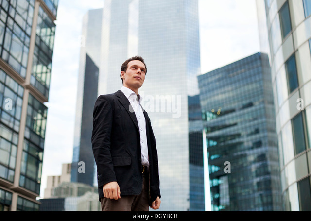 young businessman on skyscrapers background - Stock Image