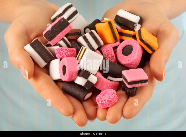 WOMAN HOLDING LICORICE ALLSORTS SWEETS / CANDIES - Stock Image