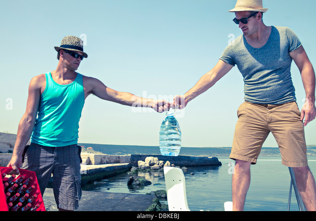 Croatia, Dalmatia, Young men at the seaside, transporting beer - Stock Image