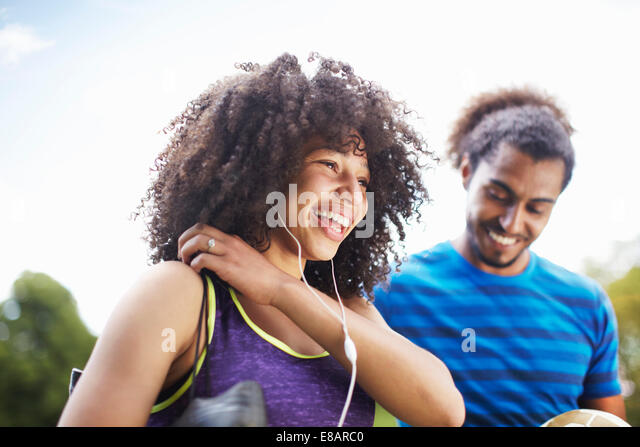 Young soccer couple laughing together in park - Stock Image