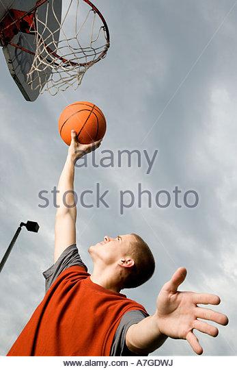 A teenage boy playing basketball - Stock Image
