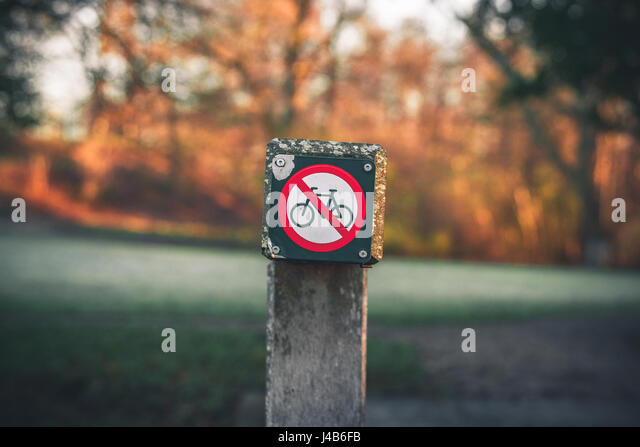 Bike restriction sign in a park in autumn with no bike riding allowed - Stock Image