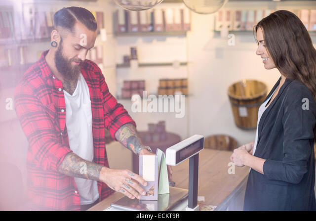 Owner weighing candies in front of customer in shop - Stock Image
