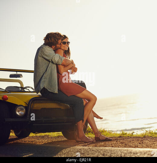 Young couple in love embracing and kissing. Young man and woman sitting on their car hood. Romantic young couple - Stock Image