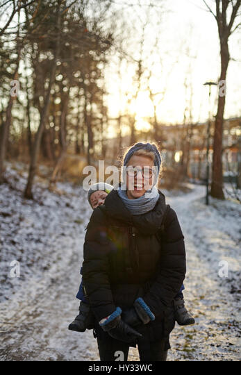 Sweden, Sodermanland, Stockholm, Johanneshov, Hammarbyhojden, Laughing mid adult woman carrying son (2-3) - Stock Image