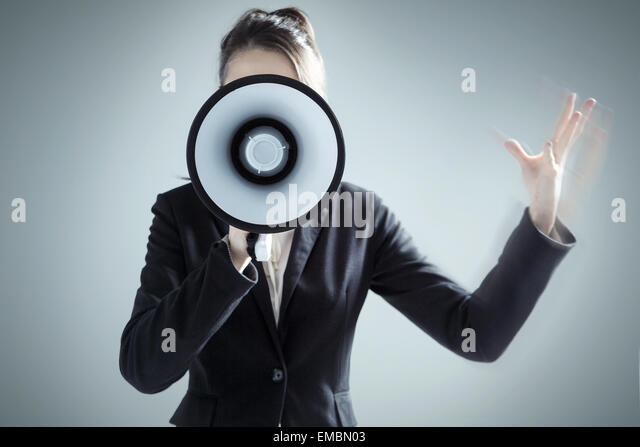 Young pretty businesswoman yelling over megaphone - Stock Image