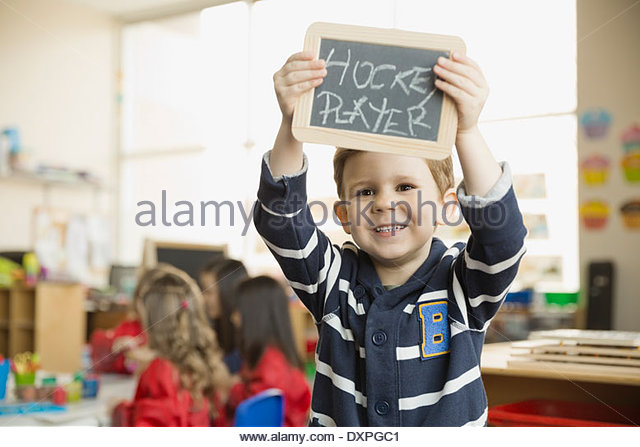 Smiling boy holding slate with 'Hockey Player' written on it - Stock Image
