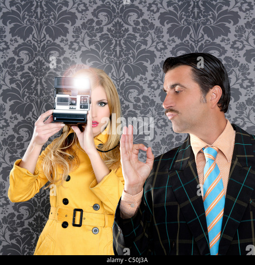 geek tacky mustache man reporter fashion girl photo shoot retro wallpaper - Stock Image