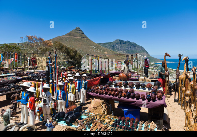 Souvenir dealer selling carvings along Victoria Road, Cape Town, South Africa - Stock Image