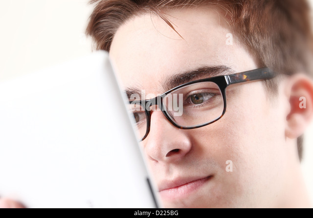 Young male wearing glasses looking at the screen of his laptop or digital tablet. Close up on eyes. - Stock-Bilder