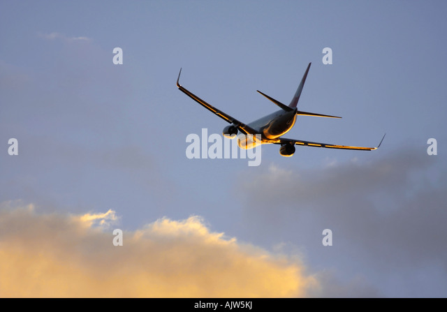 Passenger airplane in flight in reflecting sunset light. - Stock Image