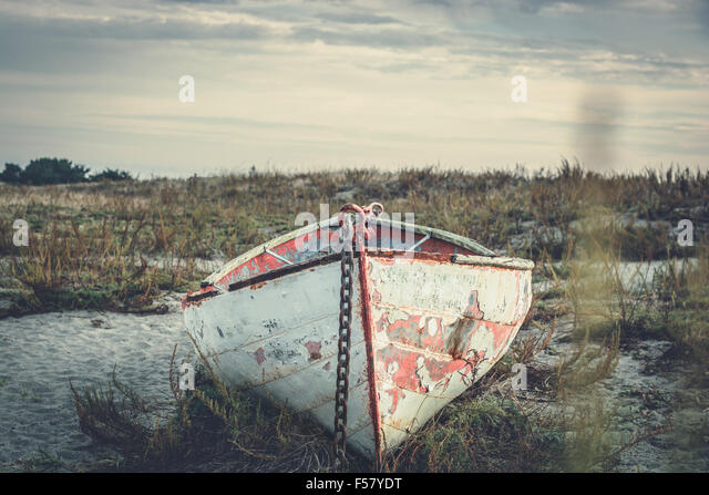 Old rowboat sits on an empty beach - Stock Image