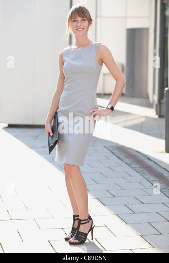 Germany, Bavaria, Munich, Young businesswoman holding purse, smiling, portrait - Stock Image