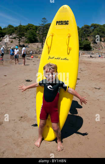 Young boy holding yellow surfboard on beach at Horseshoe Bay in Port Elliot South Australia - Stock Image