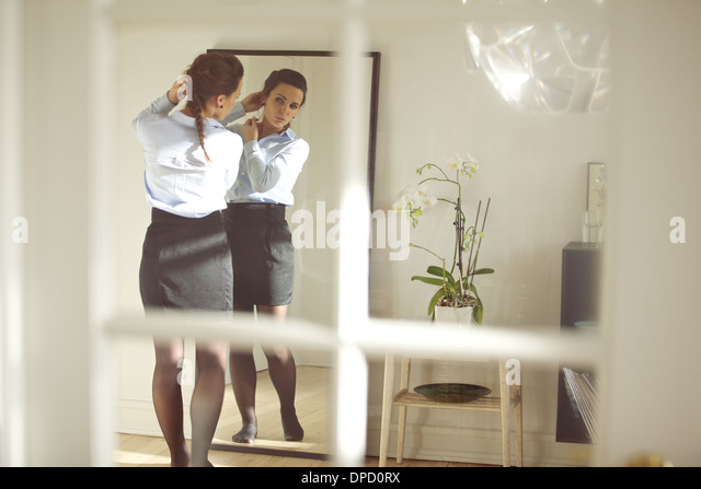 Beautiful business woman getting dressed for work in front of mirror at home. Caucasian female model in business - Stock Image