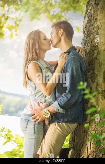Couple in love on the lake, beneath the trees, kissing - Stock-Bilder