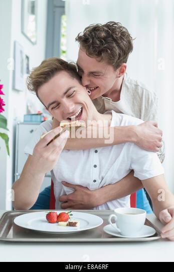 Homosexual couple having breakfast together, smiling - Stock-Bilder