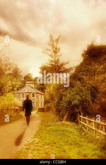 Man walking towards house in the countryside - Stock-Bilder