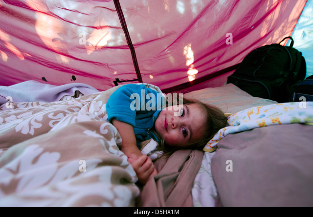 Little girl inside a camping tent lying happy on sleeping bag. - Stock-Bilder