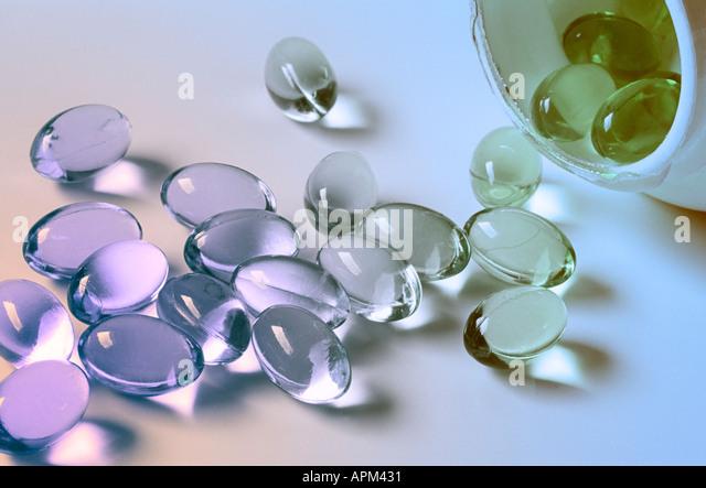 Cod Liver Oil capsules spilling out of bottle sidelit in pastel colours - Stock-Bilder