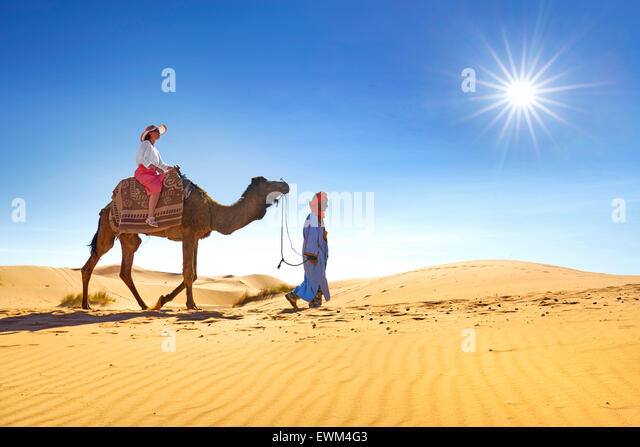Tourist on camel ride, Erg Chebbi desert near Merzouga, Sahara, Morocco - Stock Image