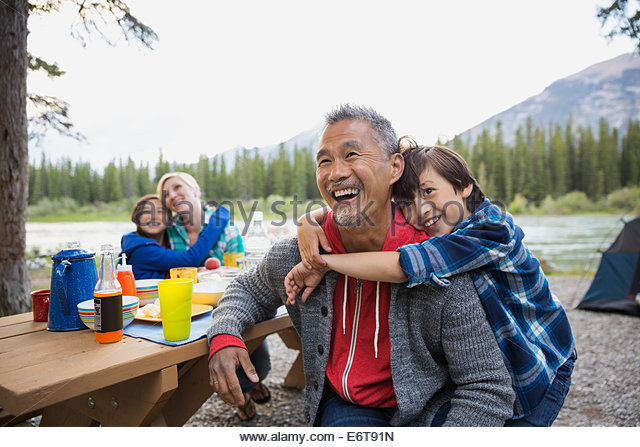 Family relaxing together at campsite - Stock-Bilder