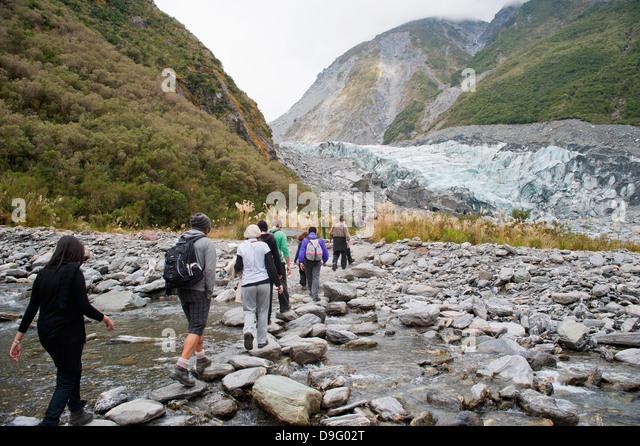 Tourists on Fox Glacier trek, Westland National Park, UNESCO World Heritage Site, South Island, New Zealand - Stock Image