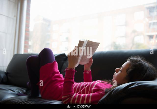 Girl lying on sofa, reading book - Stock-Bilder