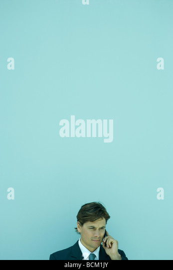 Businessman holding cell phone to ear, head and shoulders - Stock Image