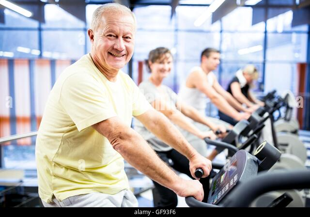 PROPERTY RELEASED. MODEL RELEASED. Portrait senior man exercising on stationary bicycle in gym. - Stock Image