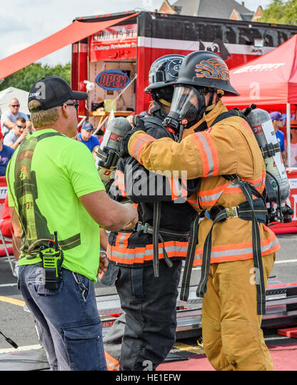Firefighters hug before competition event. - Stock Image