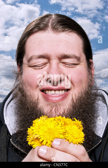 Happy bearded man with yellow flowers - Stock Image