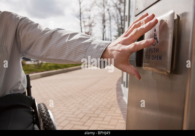 Businessman with spinal cord injury in a wheelchair pushing a button to open a door - Stock Image